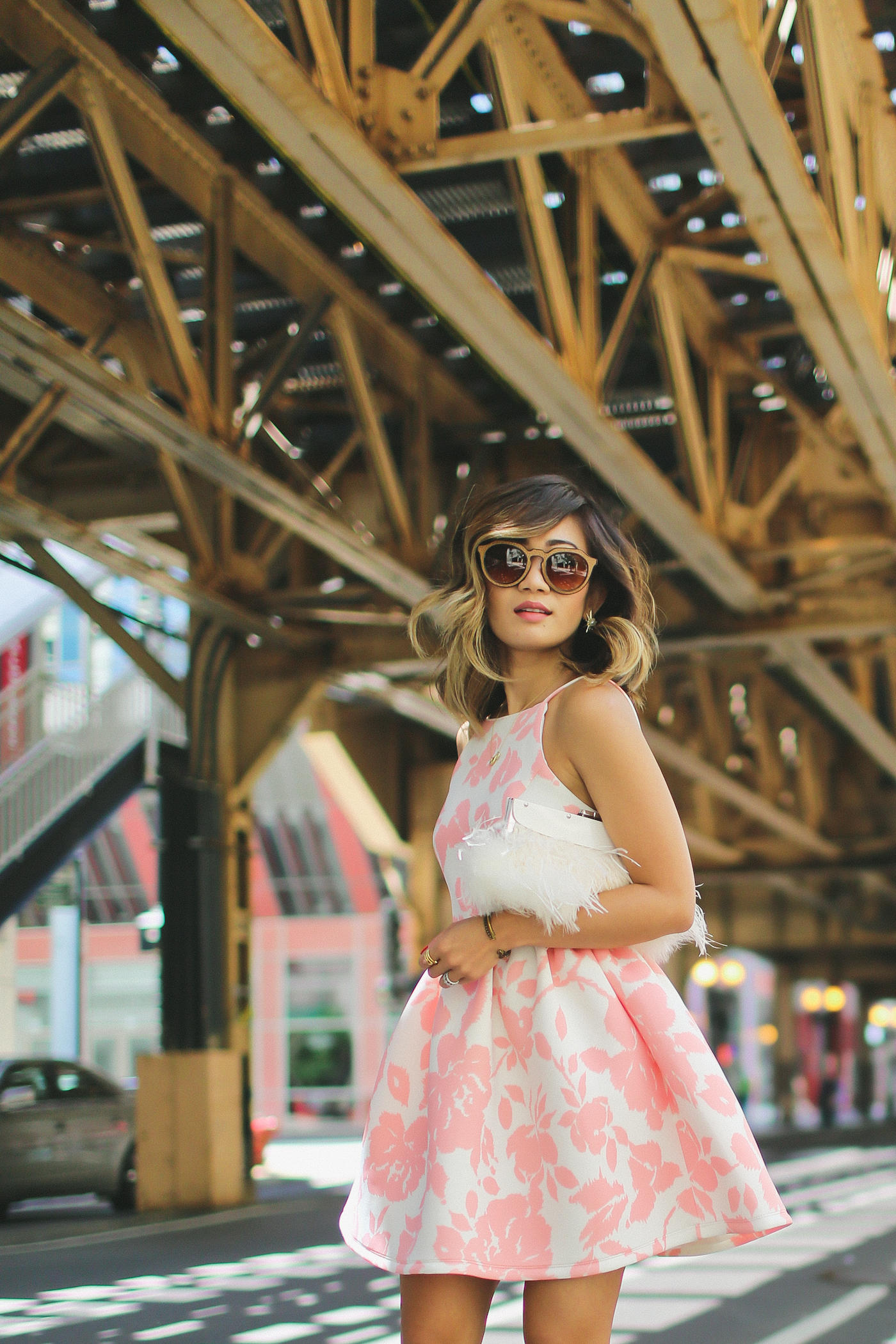 pink floral print flare dress from generation bliss and bcbg feather clutch